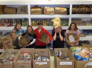 Freshmen students, Torrie Landgraf, Amy Schattel, Rebecca Brown, Rachel Wadell, Erica Strope, and Sarah Sleevi, spent a Saturday at Catholic Neighbor-good sorting through thousands of donations with other WJU students.